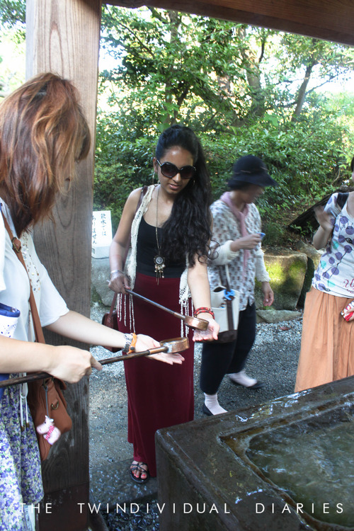 Our host Shiori showing Hernoor how to wash her hands the traditional way, before we go and see Buddha.
