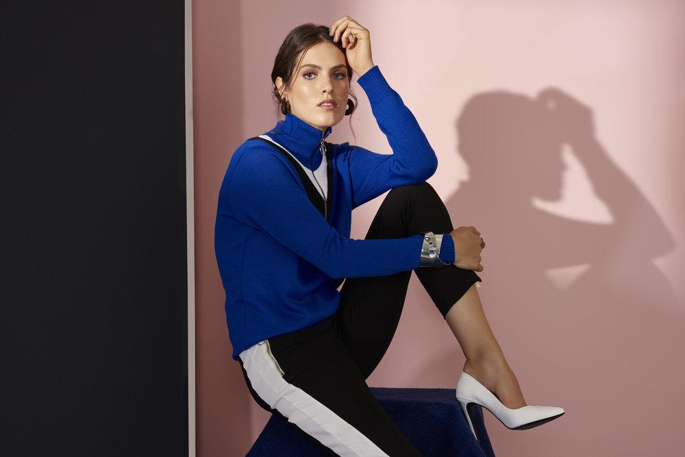 Mulher vestindo suéter azul e scarpin branco.