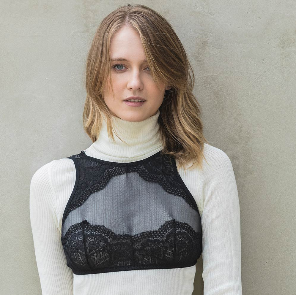 Mulher usando lingerie por cima da blusa