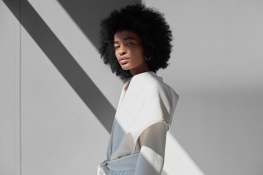 Modelo vestindo um casaco oversized branco da AMARO
