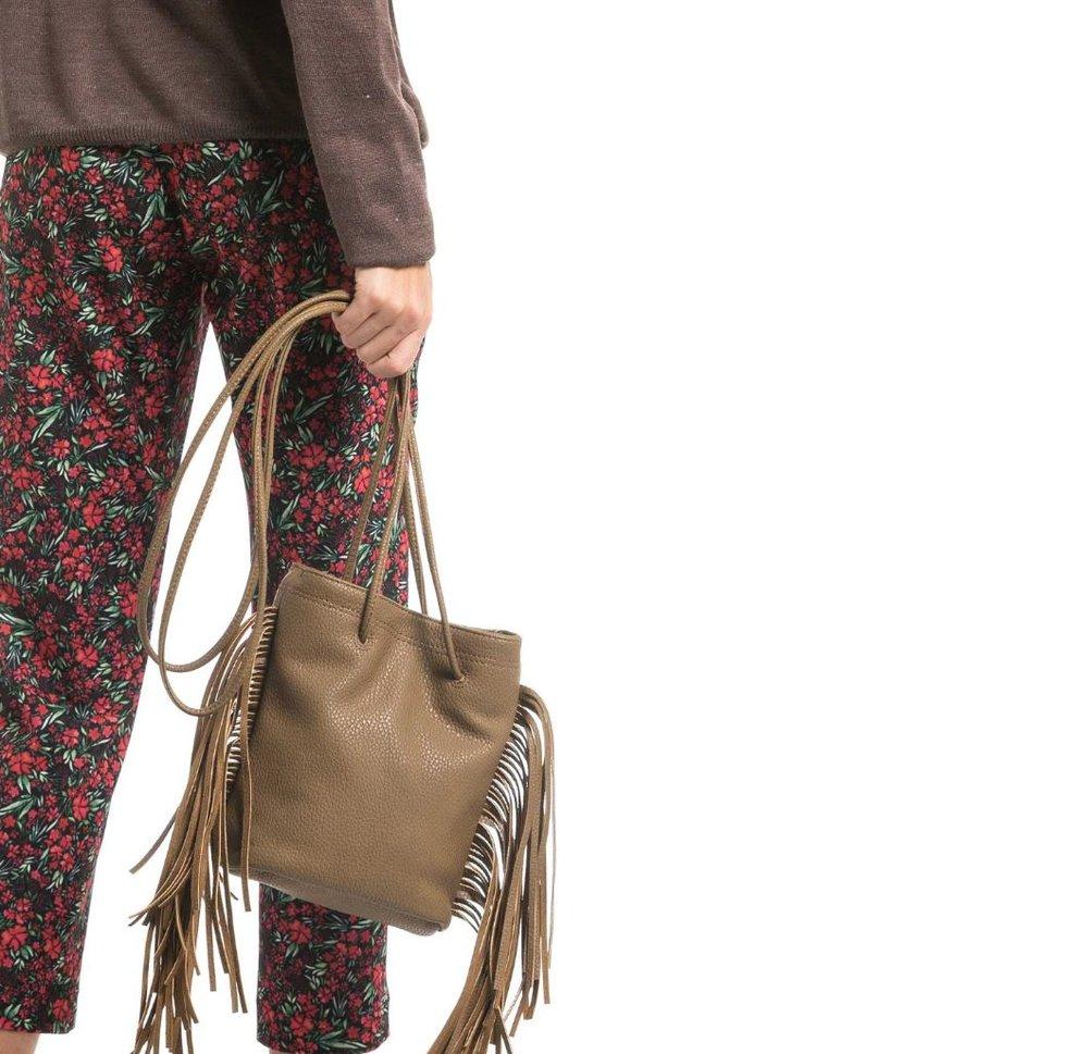 Modelo segurando uma bolsa com franjas na cor marrom