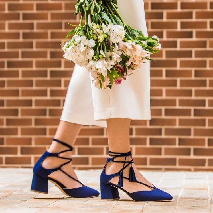 Foto de modelo calçando scarpin azul e calça pantacourt nude.