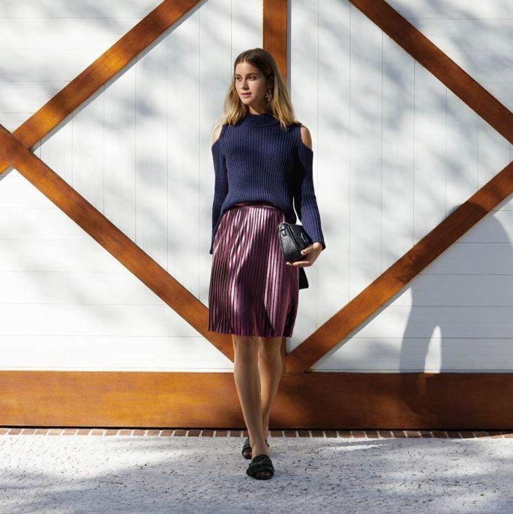 Modelo vestindo saia plissada rosa e suéter azul AMARO
