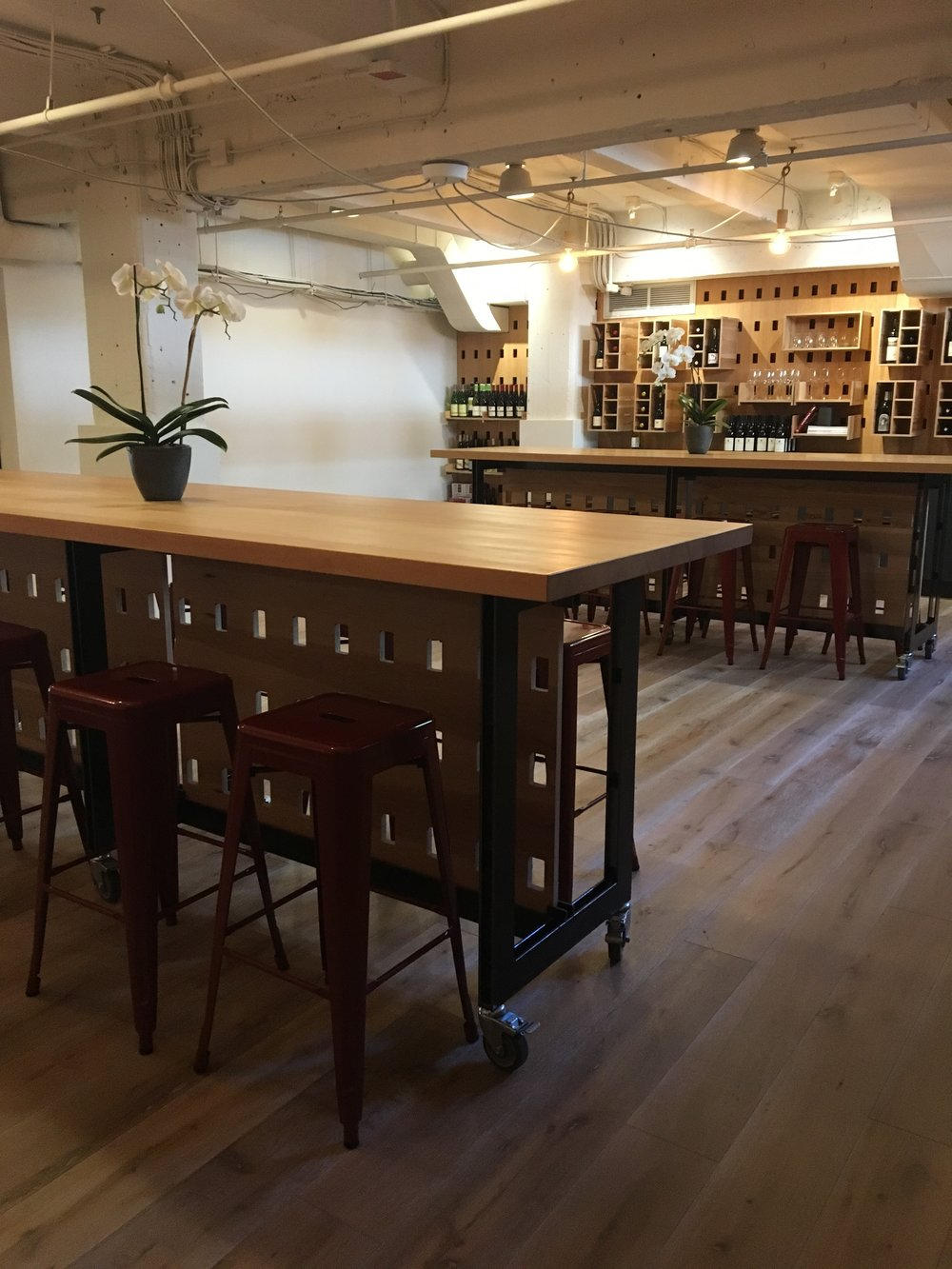 Your private wine cave - A special events space/tasting room is available to rent at the back of Mayhew Wine Shop.  It is accented by sliding barn doors that can be open to the rest of the shop or closed for a more private feel.  The tasting room has 2 large rustic wood tasting tables, custom cabinetry and surfaces, and can accommodate up to 50 people.  The original stone wall in the room creates an authentic wine cave feel.