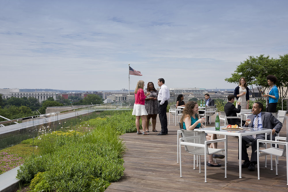 Groups seated at patio tables and standing, with skyline in background