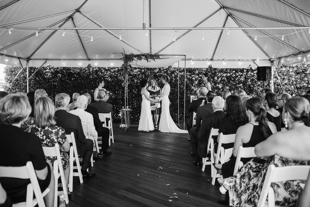 Engaged couple taking making wedding vows during ceremony, with attendees seated in foreground