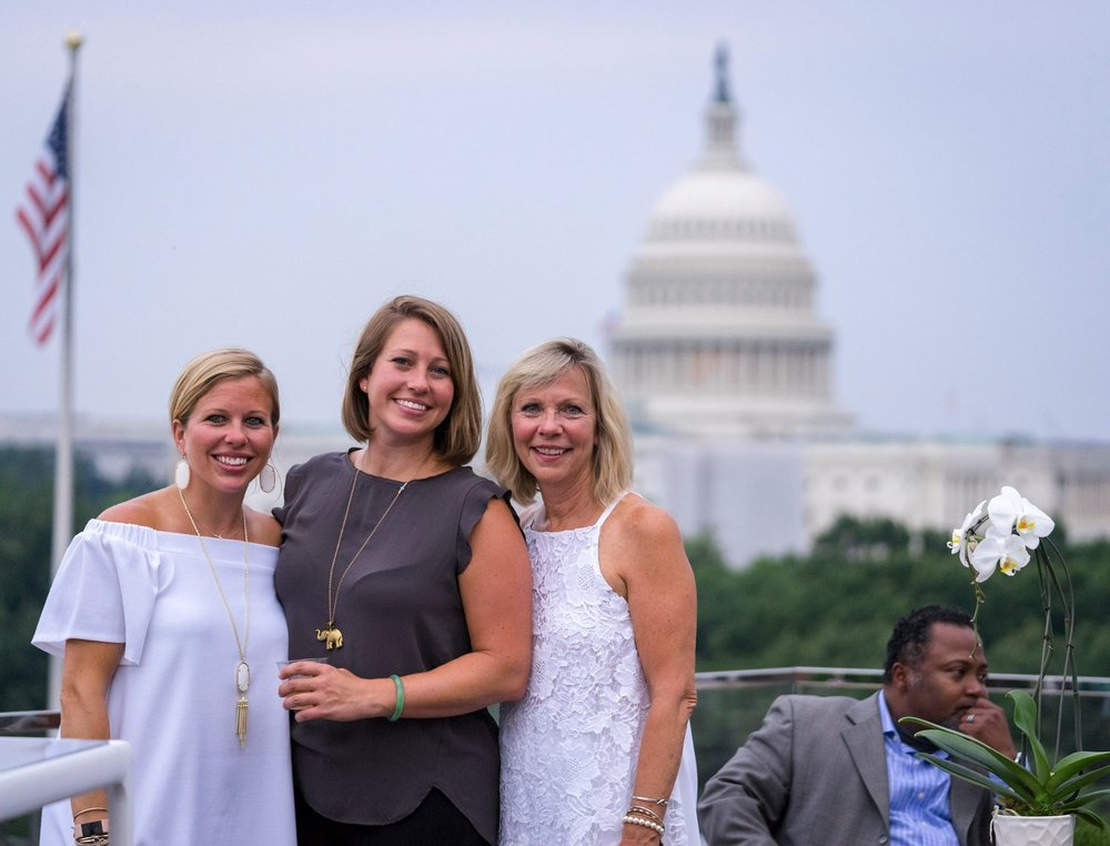 Three women posing for group photo, with Capitol building in background