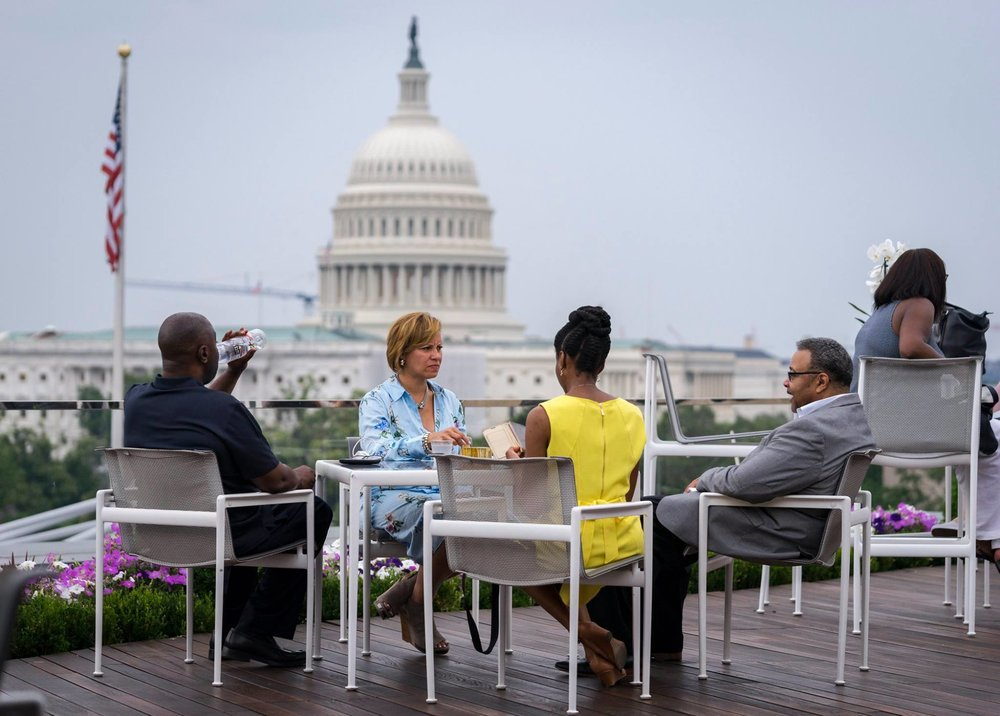 Group sitting at patio table on rooftop deck, with Capitol building in the background
