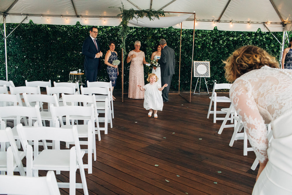 Bride at altar visiting with guests, while young girl runs down the aisle to her mother