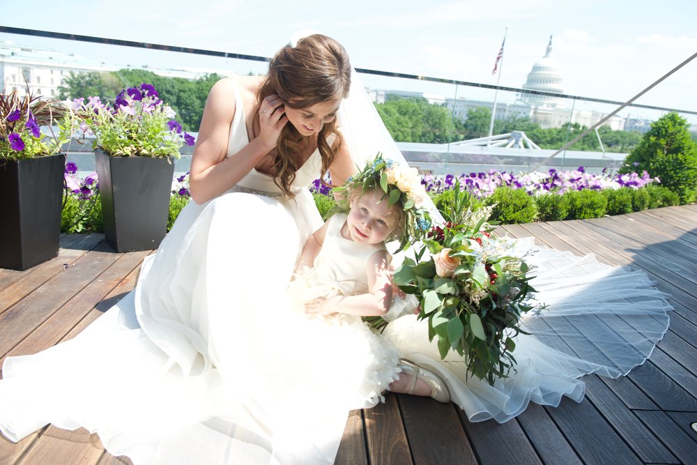 Bride with young flower girl posing on rooftop deck, with Capitol building in background.