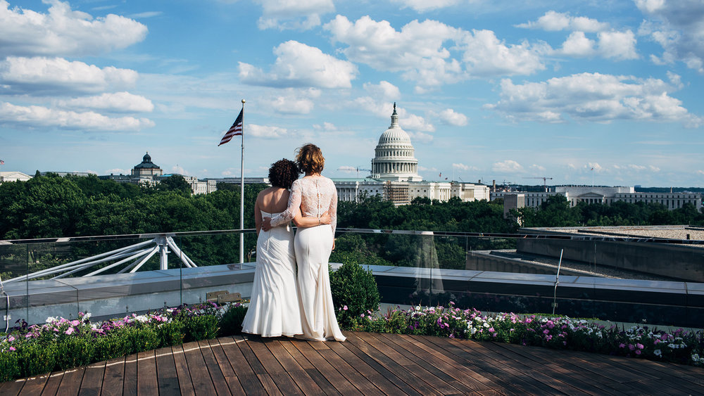 Engaged couple taking in view of Capitol building at their wedding at the rooftop event space