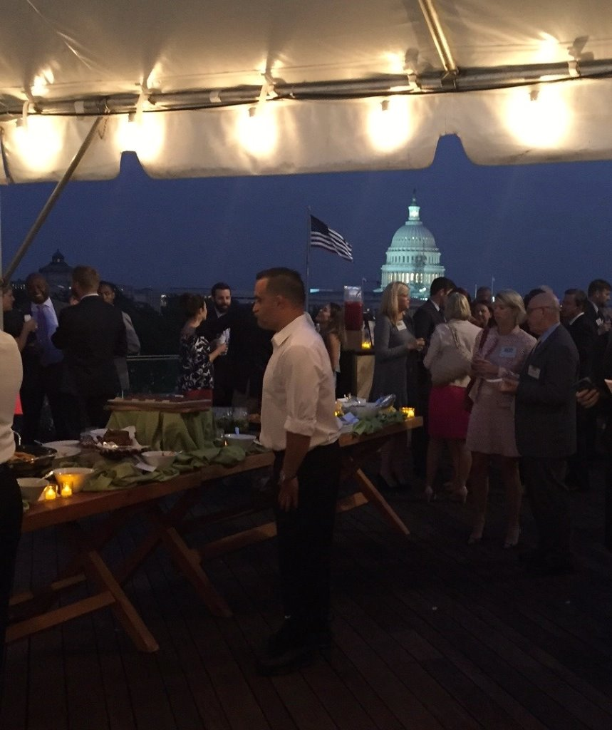 Event gathering with table of catered food, and Capitol building in background