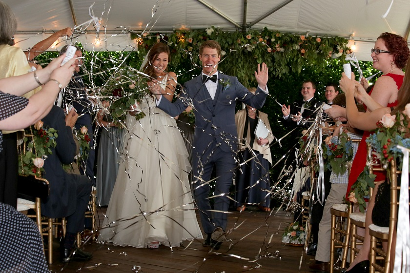 Wedding attendees throwing tinsel at couple as they walk down the aisle