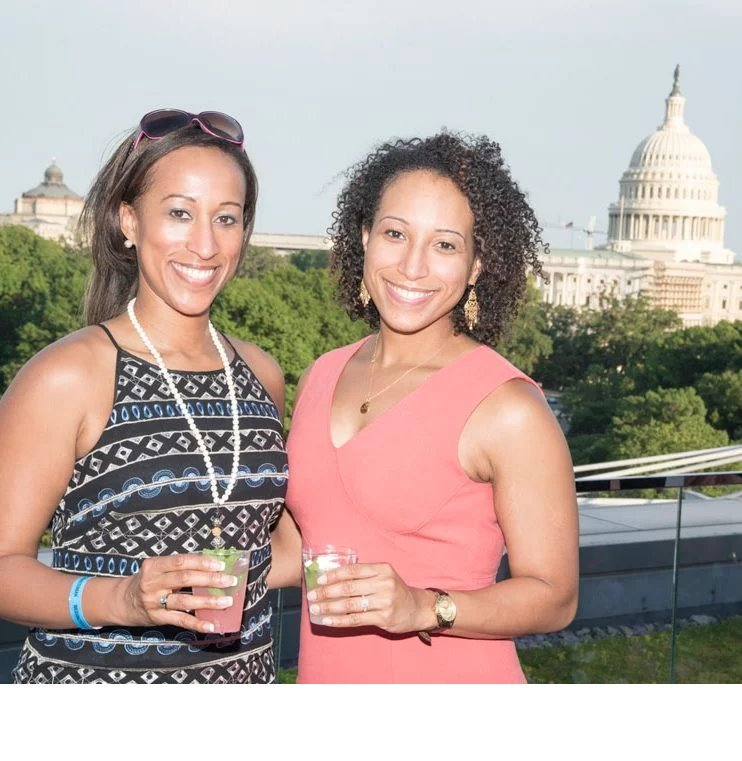 Two women posing for photo, with Capitol building in background