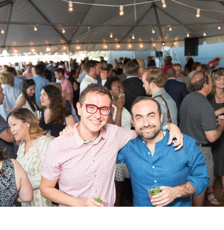 Two men posing for photo, with event crowd in background in tented event space