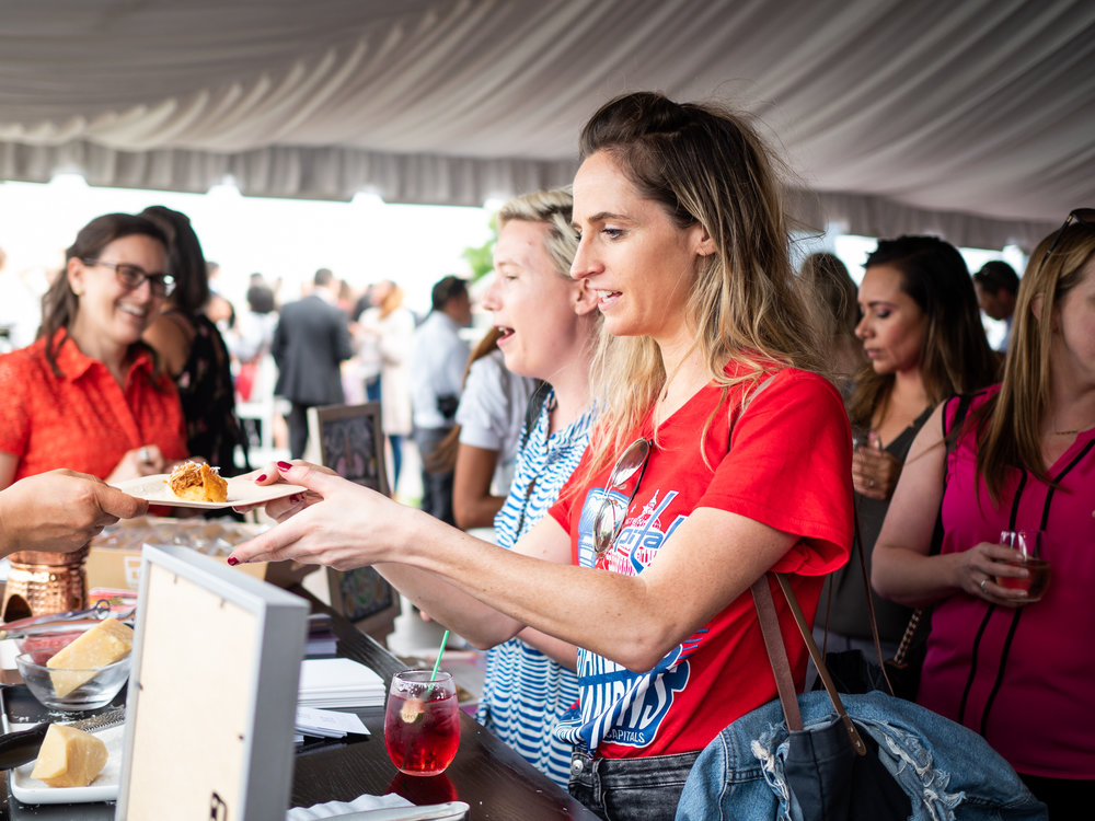 Woman accepting plate of food at catered event, with other guest in line behind her