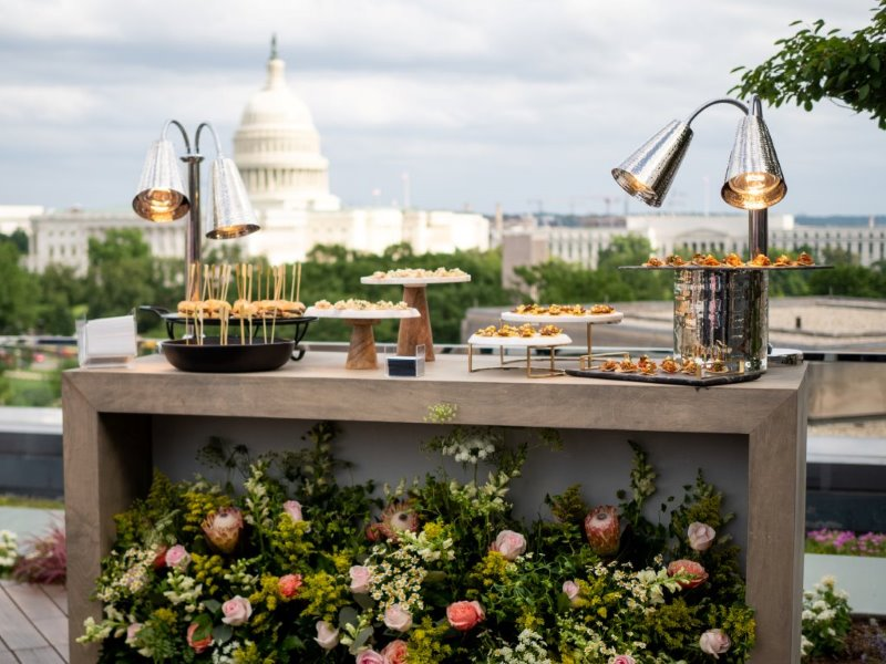 Table of catered food and floral arrangements, with Capitol building in background