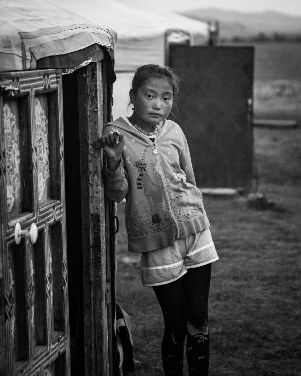 Photo by Daniel Fast  Buyan's cousin, Nomin stands outside a ger used for guests at the family's camp. The Ger to Ger organization finds guests for the family, as a way to help supplement their income as livestock herders. Orkhon Valley, Ovorkhangai, Mongolia.