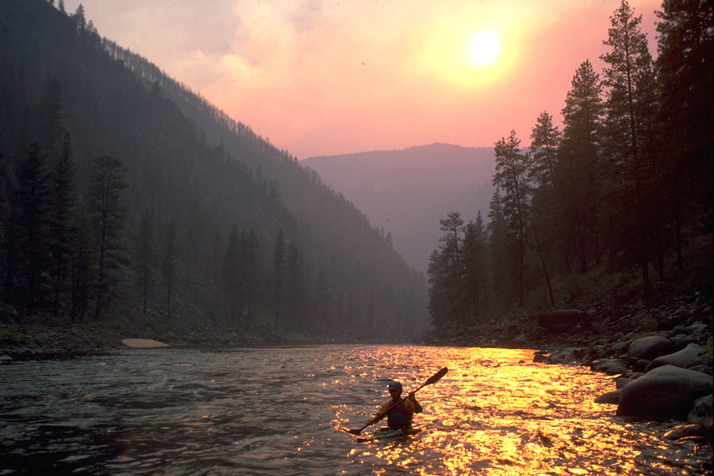 Kayaker on the Salmon River in Idaho during summer forest fire