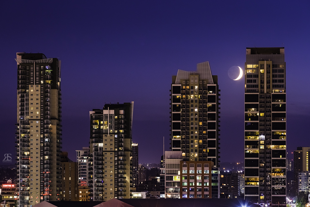 From the same location I noticed the moon was setting.  I waited until the moon sank between the two buildings.  I should've set up faster to centre the moon between the structures but by the time I took the picture the moon had moved rather quickly.  Be prepared!