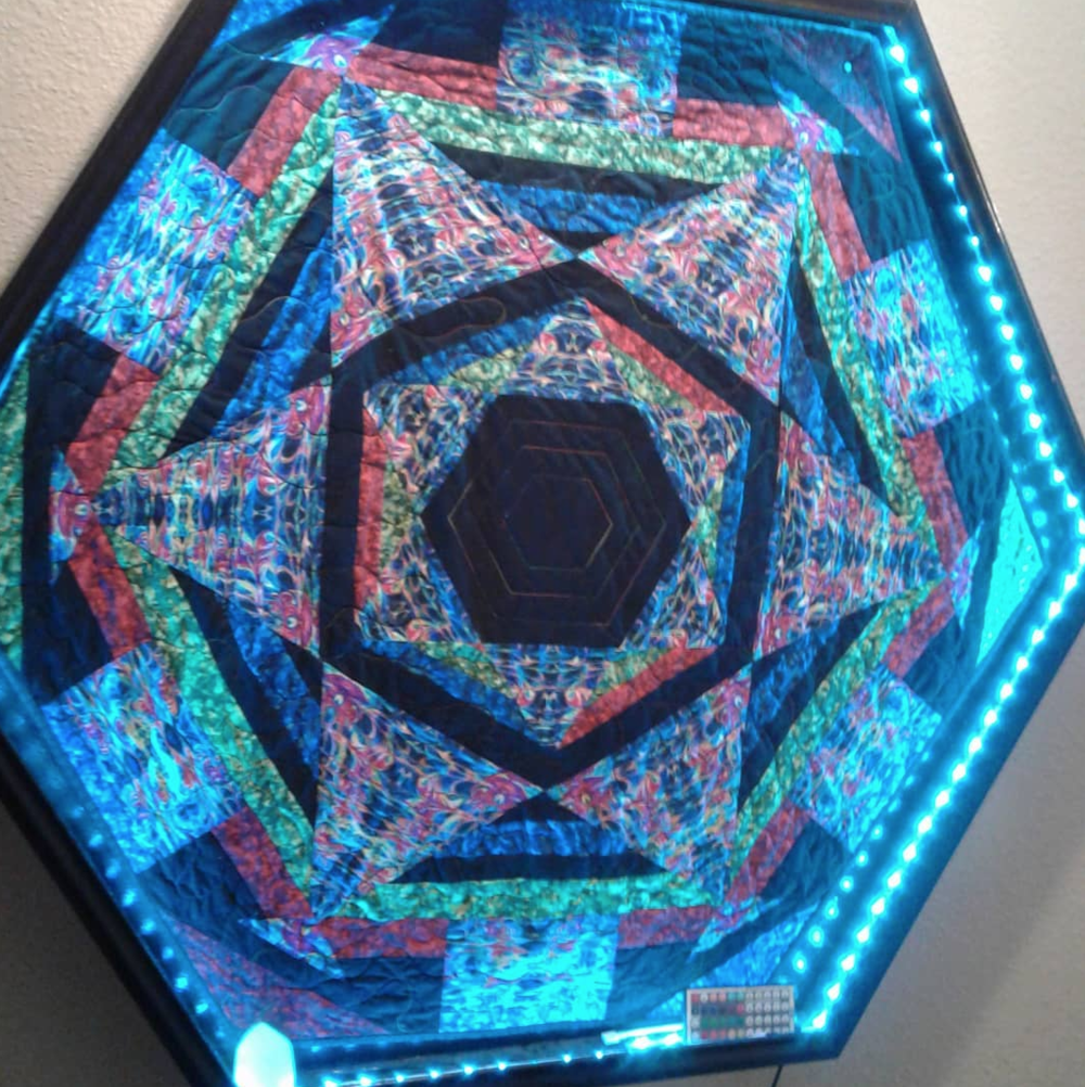 Hand-sewn quilts with color changing led lights in the frame.. as the lights change color the fabric changes and warps!