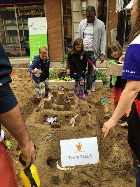 """Team TELUS puts the finishing touches on its sandcastle."""