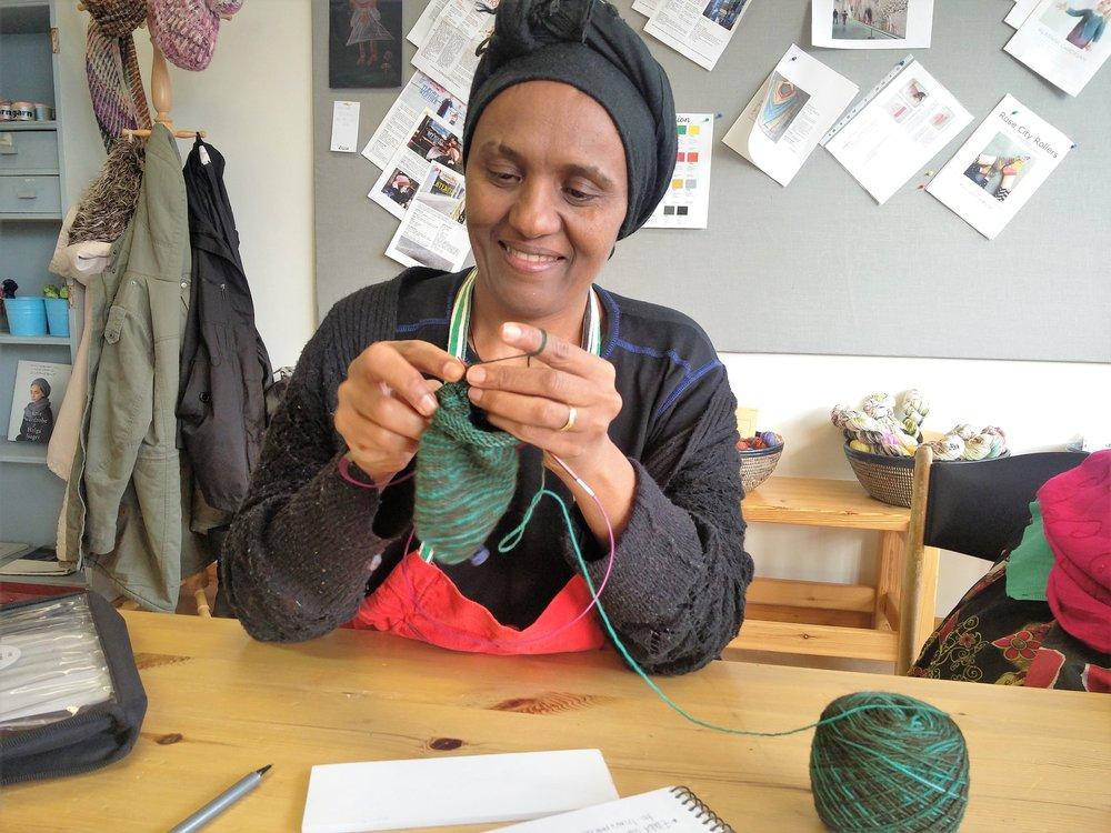 I morgen begynner Akberet fra Eritrea, og det gleder vi oss helt vilt til! Hun kan, som dere ser, allerede strikke. Her låner hun Halimos strikketøy, sokk nummer to, og skjønte teknikken med magic loop med en gang:-) Hun kan også sy, så nå lurer vi litt på om vi skal finne på noe vi kan sy og selge i tillegg.