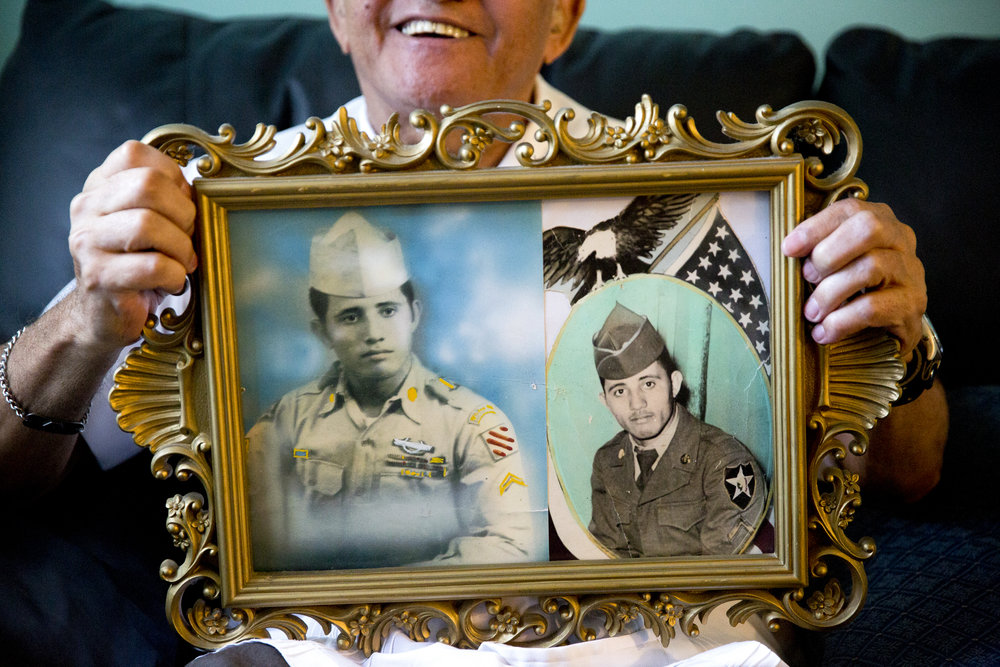 Army veteran and Naples resident Jose A. Santos-Rolon holds up a picture frame with two photos of his younger days in the service at his home in Golden Gate Estates Friday, April 8, 2016. Santos-Rolon will receive the highest civilian honor the United States Congress can award, the Congressional Gold Medal of Honor, for his service in the Korean War with the 65th Infantry Regiment based out of Puerto Rico. Santos-Rolon, along with his wife, Carmen, and the remaining members of his regiment, will travel to Washington D.C. to receive the Medal of Honor April 13, 2016.