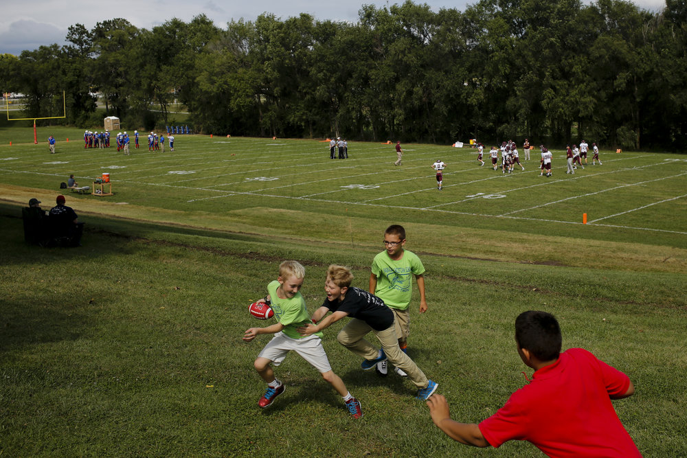 Children play their own pick-up game of football minutes before Parkview Christian football hosted Lyons-Decatur Northeast Friday August 28, 2015 at Parkview Christian High School in Lincoln, Nebraska.