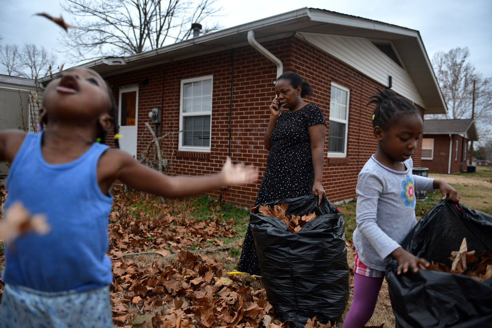 "Liberian refugee Shirley Bargblor takes a break from bagging leaves with her granddaughter's (L to R) Kwametee, 3, and Kwamena, 5, to speak on the phone with a friend. ""They can be a handful sometimes,"" Shirley said. Along with their two grandchildren, Shirley and her husband Eurodger also house four of their six children in their two-bedroom apartment. Through different funds and charities the Bargblor's pay nothing to rent the apartment which is part of the Public Housing Authority in Bowling Green, Ky. ""It is a gift from God,"" Shirley said. Both Shirley and her husband attend Western Kentucky University part-time and are on track to receive their business degrees."