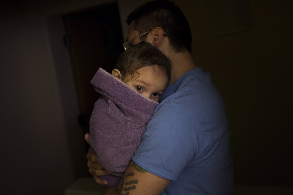 Wrapped tightly in a warm bath towel with head burrowed in his father's arms Stellan Gonzalez, 1, stares on with sleepy eyes as his father Fred Gonzalez Jr. carries him to his room to prepare for bed October 22, 2014 in Berea, Ky.