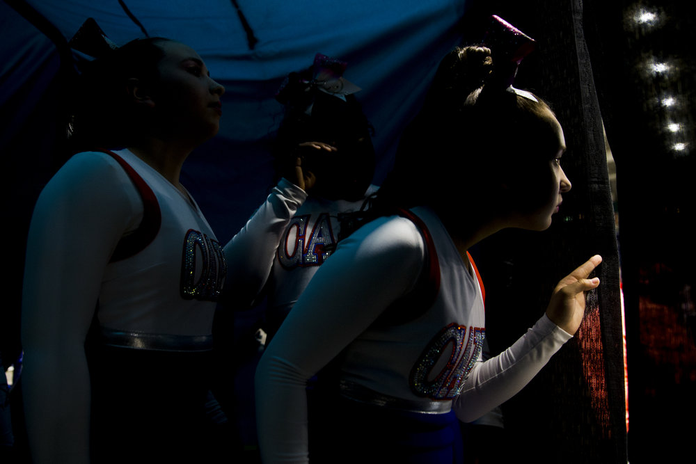 Emylee Gonzalez, 13, anxiously peers out to the arena floor as her squad, the Cape Coral Junior Varsity cheer team, prepares to perform their routine during the Peace River Conference Pop Warner Cheerleading Competition at Germain Arena Sunday, October 22, 2017 in Estero, Fla. Teams throughout the region came to support their hometowns in the event.