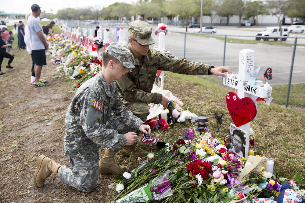"""Florida Atlantic University ROTC cadets Armand Vezina, left, and Steven Todd White pay their respect to Peter Wang, a JROTC student who lost his life during last week's school shooting, at Marjory Stoneman Douglas High School Tuesday, Feb. 20, 2018 in Parkland, Fla. """"Once I heard about Mr. Wang's passing and holding the door open we had to come,"""" Vezina said. """"He deserves the utmost respect."""""""