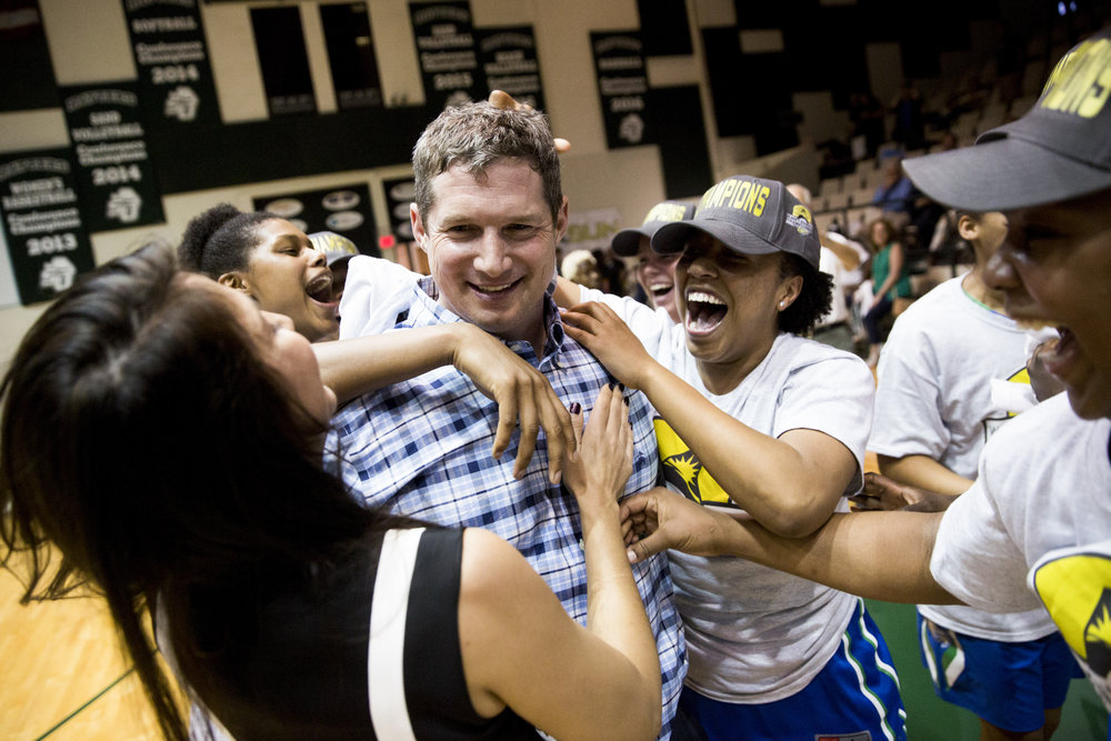 The FGCU women's team swarms head coach Karl Smesko after defeating Stetson 77-70 in the Atlantic Sun Championship game at the Edmunds Center Sunday, March 12, 2017 in DeLand, Fla.