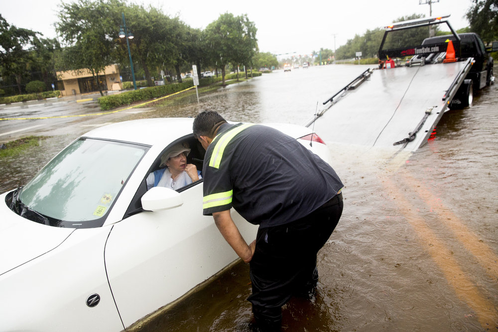 Marco Island resident Mariu Lazzaro has her car towed out by Dave Molinet, an employee of 1-800TowSafe.com, after getting stuck on Bald Eagle Drive near the corner of San Marco Road Wednesday, June 7, 2017 in Marco Island, Fla. Lazzaro, a volunteer at the Marco Healthcare Center, misjudged the height of the water as she pulled out of the parking lot.
