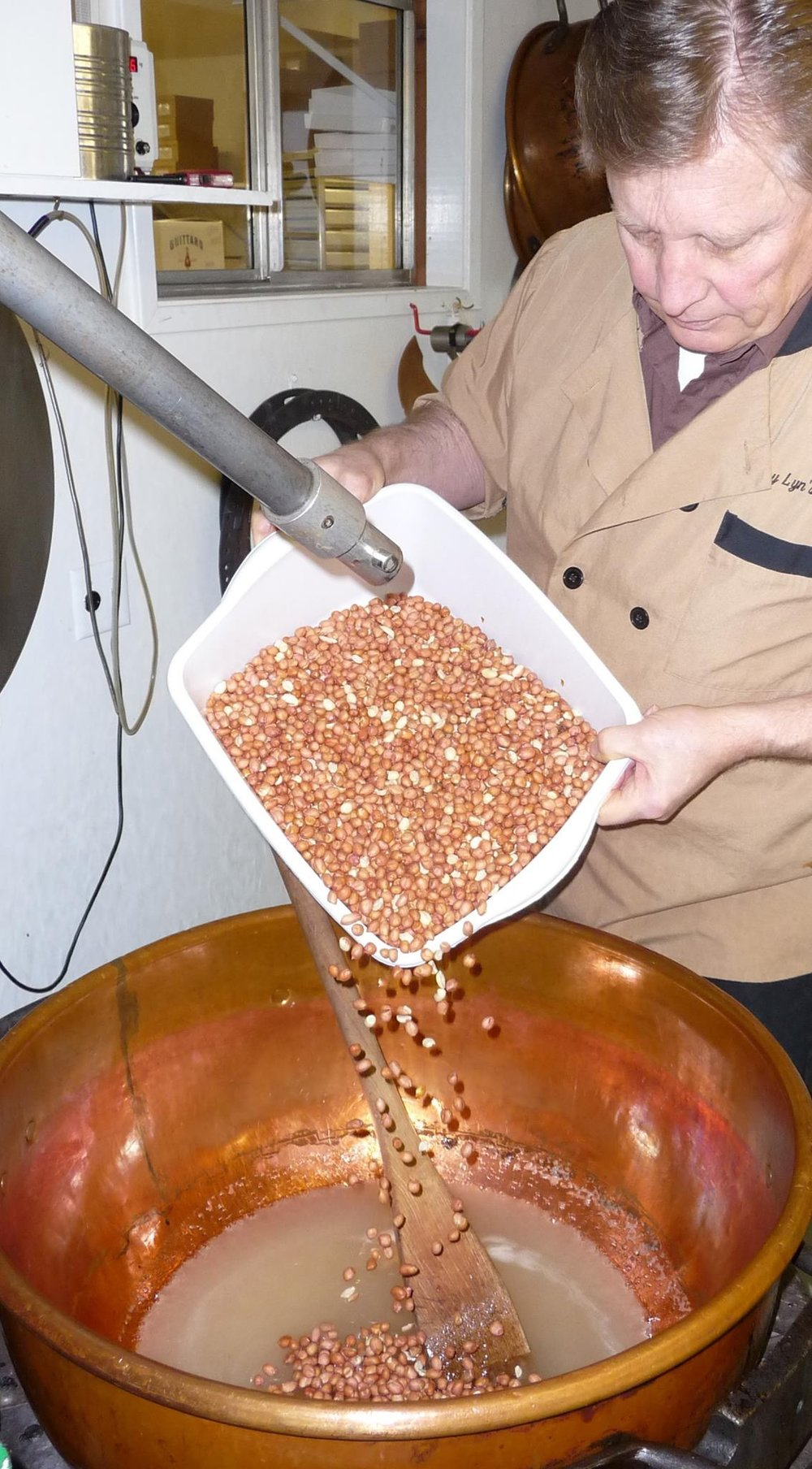 Adding the peanuts to the copper kettle for the Peanut Brittle.