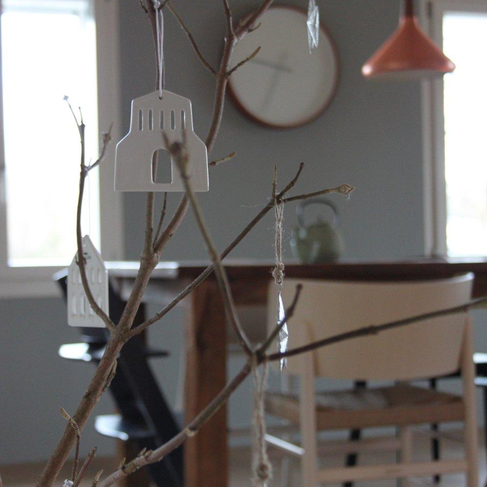 Hängende Häuser von Kähler  Am Ast hängen silbrige Sterne und kleine Keramikhäuser von Kähler Design.