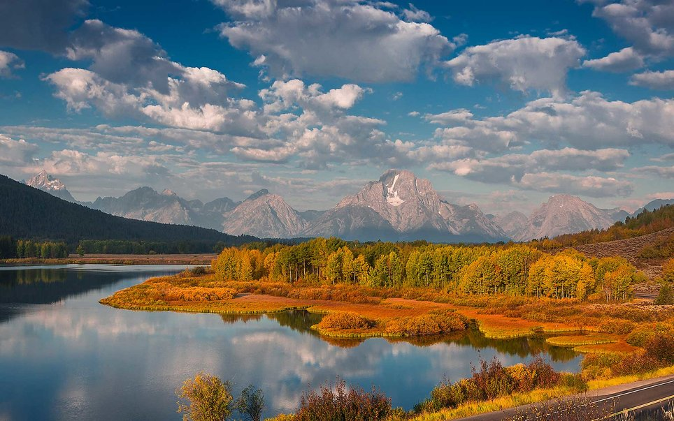 Rugged slabs of rock speckled with glaciers and snowfields protrude through the clouds, and shield the entry to Grand Teton National Park.
