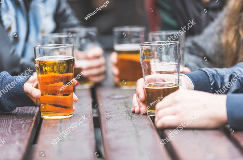 stock-photo-hands-holding-glasses-with-beer-on-a-table-at-pub-in-london-a-group-of-friends-is-enjoying-beer-318551834.jpg