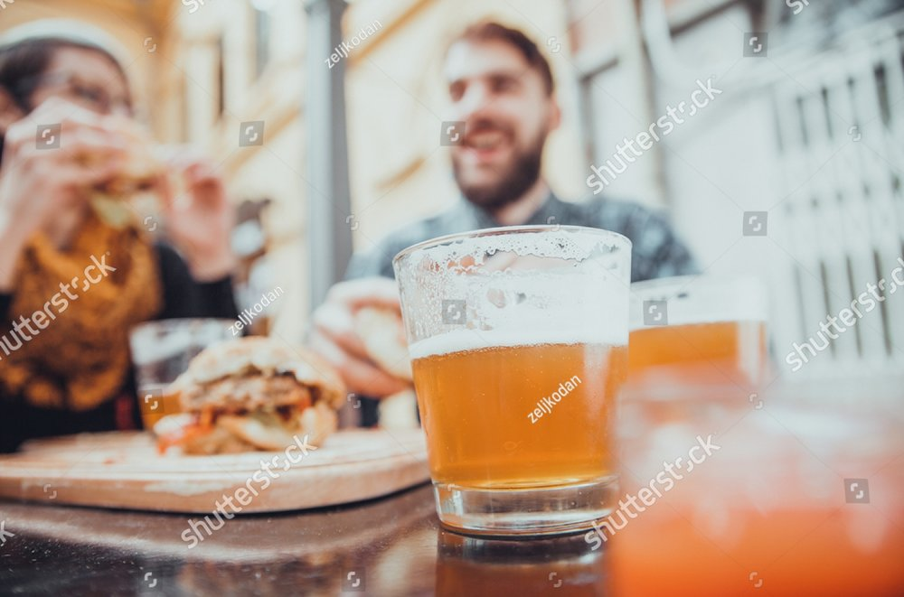 stock-photo-couple-in-fast-food-restaurant-eating-burgers-focus-is-on-glass-of-beer-371195360.jpg