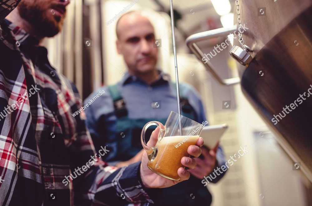 stock-photo-owner-pouring-beer-in-glass-while-standing-by-worker-at-brewery-547718470.jpg
