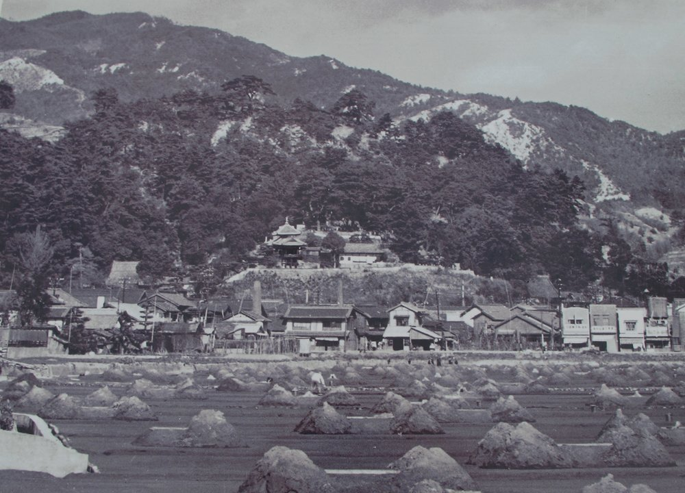 A view of the salt fields fronting what is now Takehara's historic district. At high tide, the salt fields were flooded naturally and, as the tide receded and the seawater evaporated, the salt was scooped into mounds. Salt was made like this at the town until 1960.