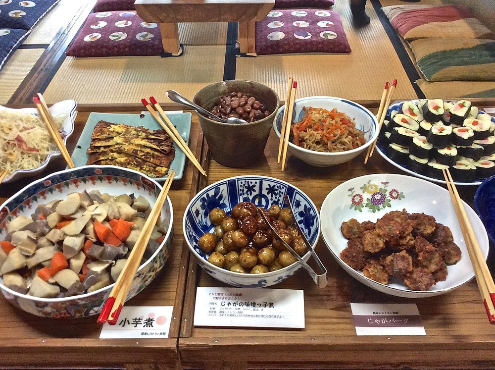 A medley of potato dishes, including shredded potato with bacon (top left), potato  futomaki  rolls (top right), potatoes braised in a  nitsuke  sauce of sake, soy sauce, and sugar (bottom center), and potato burgers (bottom right).