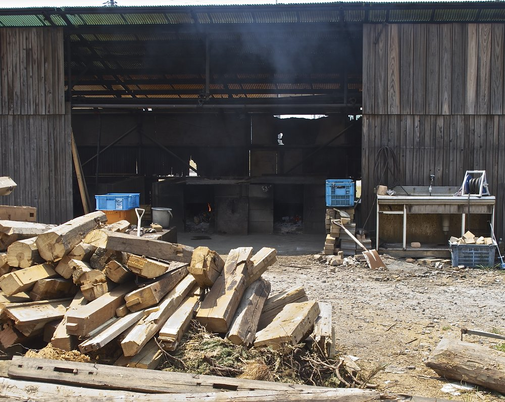 Recycled wood used to heat the salt pans piled in front of the Hamamori no Moshio salt workshop.