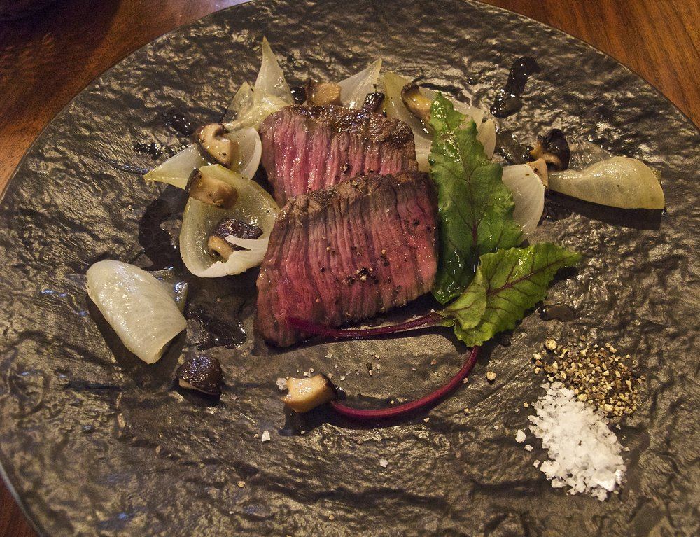 Hamamori mixed crystal white sea salt and cracked pepper served alongside Shimane wagyu beef, roasted new spring onions and shiitake mushrooms, and beet greens at Ajikura restaurant in the market town of Onan located high in the mountains of Shimane prefecture.