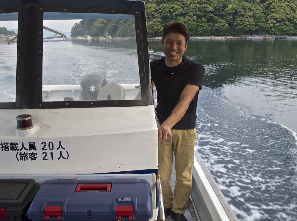 Tsugichika Kura operates a sea taxi service as well as his guesthouse and will take guests across the bay to Wadatsumi resaurant to have dinner there instead of at the  funaya,  if they choose.