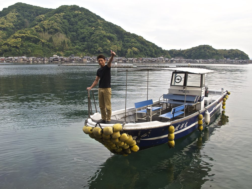 Local fisherman and innkeeper Tsugichika Kura giving an all-clear sign after having dropped guests off for dinner at Wadatsumi.