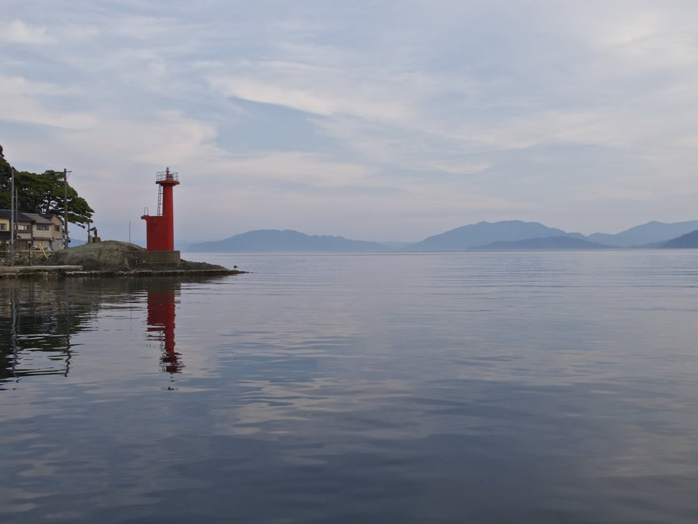 A red lighthouse marks the point where the tranquil mirror-like waters of Ine Bay meet the Sea of Japan.