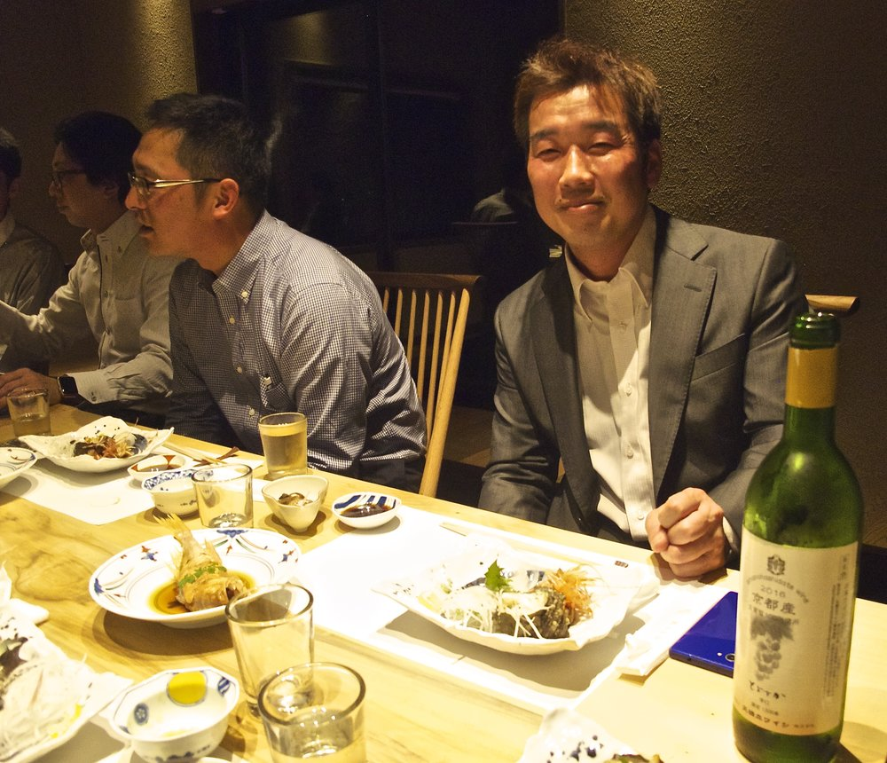 Fishermen and managers of Wadatsumi, Hiromu Hashimoto (left) and Kengo Kagi (right) celebrate the opening of the restaurant in April 2017. Kengo also operates a guesthouse at his family's  funaya , or boathouse-residence.