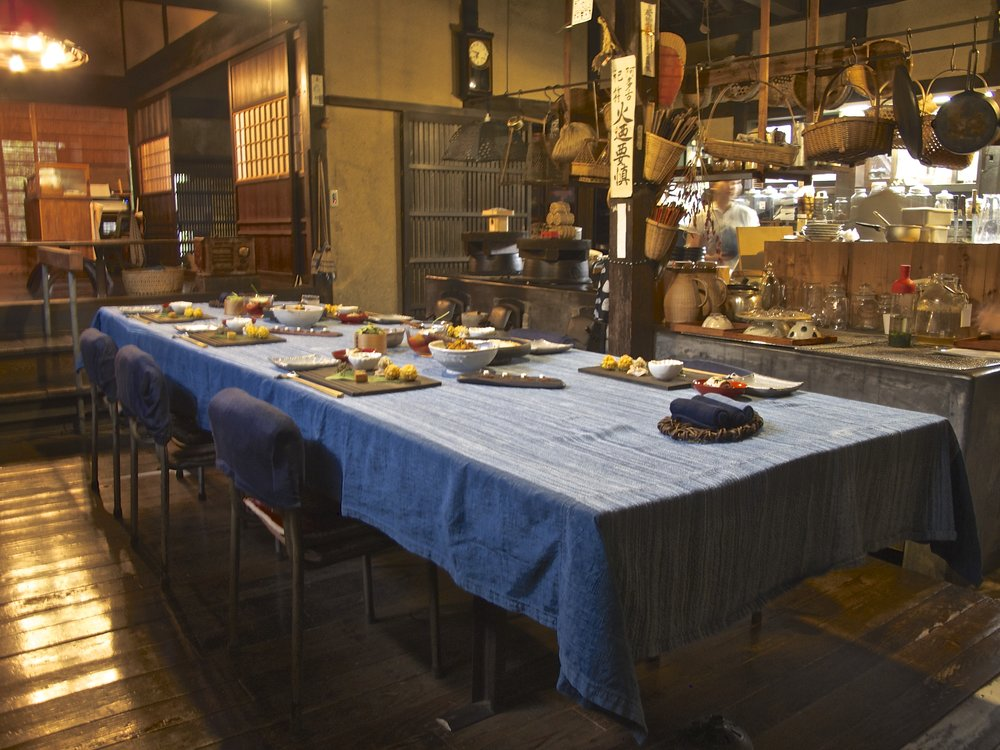 The table in the  daidokoro , the large combined cooking and eating area of the house, being set for dinner with an array of hot and cold dishes.Behind the table is the  kamado , the traditional low wood-burning stove, which separates the eating and cooking areas.
